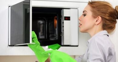 Девушка моет микроволновую печь